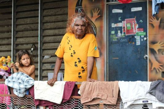 photo of Helen-Firth leaning on verandah rail full of drying clothes, small Aboriginal child is to right, Helen is wearing a yellow t-shirt with black footprints, in the background door with posters/stickers, besser bricks either side of door Aboriginal hand paintings
