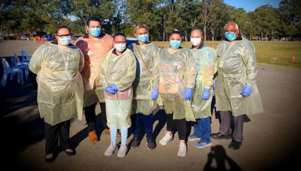 7 health professionals with gloves, gowns & masks standing on road