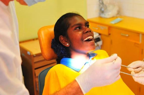 teenage Aboriginal girl in dental chair with mouth open smiling, gloves hands with instruments, masked dental professional, yellow tones