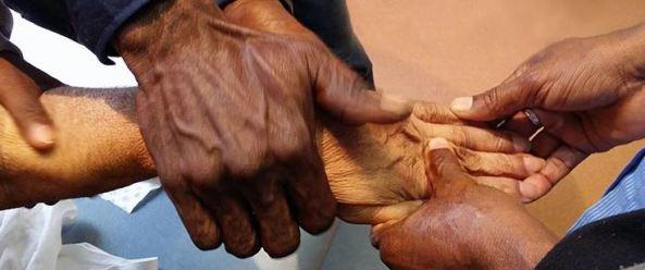 4 Aboriginal hands holding another Aboriginal hand