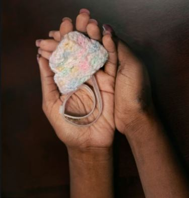 miniature baby beanie held in a woman's hands