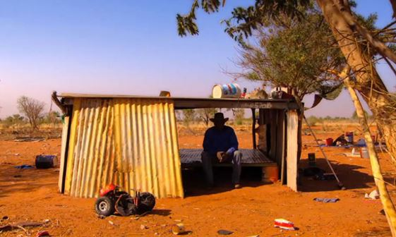 Aboriginal man sitting inside corrugated iron humpy in Utopia, no facial features visible as face is in shade