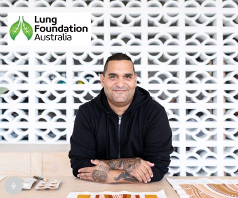 Aboriginal man with black hoodie sitting at desk with Aboriginal dot paintings, logo superimposed text 'Lung Foundation Australia' with two green leaves with veins representing lungs