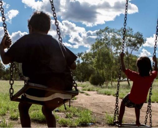 rear view of 2 Aboriginal children on swings