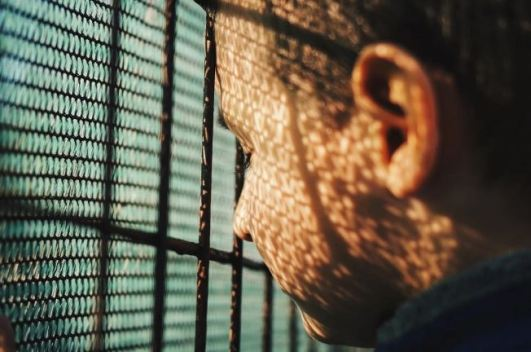 head of youth eyes closed against wire fence of jail