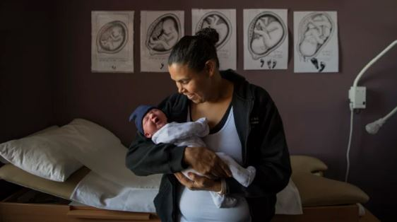 Aboriginal woman smiling at tiny baby in her arms in health clinic room with examination bed & 5 images of growing baby in womb on wall