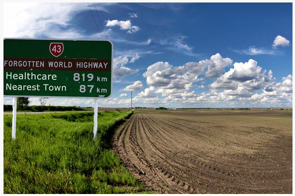 green highway sign text '43 Forgotten World Highway, Healthcare 819 km Nearest Town 87 km' sitting in green grass to side of ploughed field blue sky white fluffy clouds