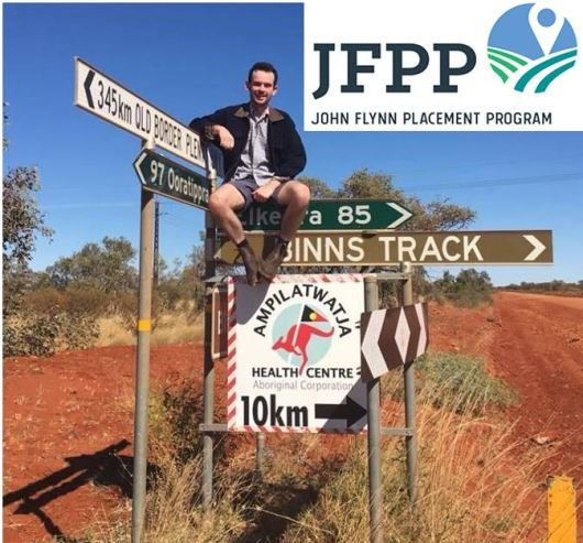 young rural doctor sitting on top of group of road signs in outback, one sign says 10 km to Ampilatwatja Health Centre Aboriginal Corporation