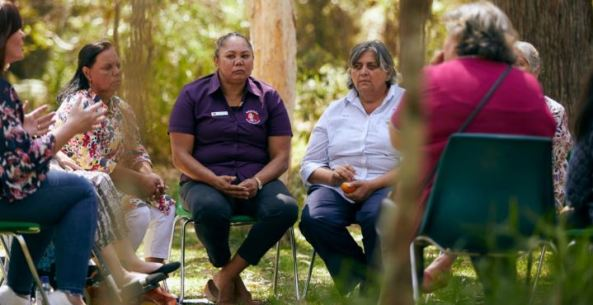 7 Aboriginal women sitting on chairs in circle in bush setting