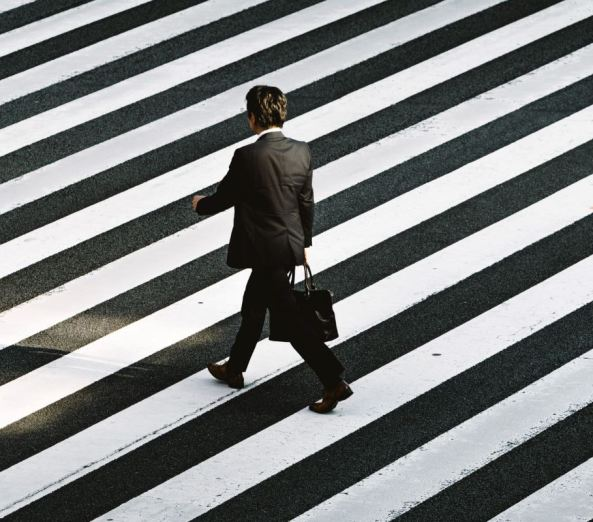 back of businessman in a suit with briefcase walking across black & white striped road