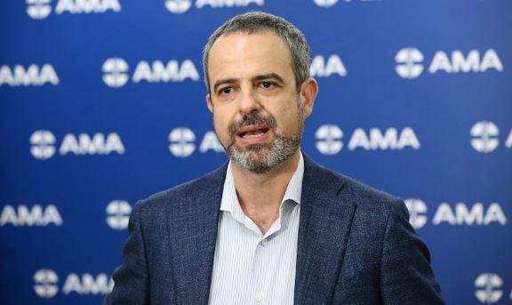 AMA President Dr Omar Khorshid standing against blue banner covered in AMA logo