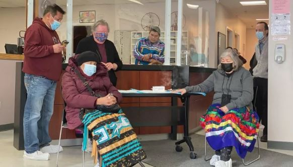 norther Alberta Canada medical reception room, masked Kehewin Cree Nation elders pray at a ceremony marking the arrival of COVID-19 vaccine; two female elders are sitting with colourful traditional rugs across knees