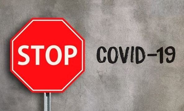 red stop sign, grey background & black chalk font writing 'COVID-19'