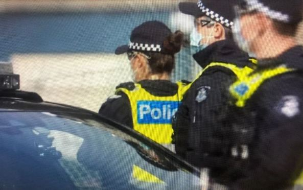screenshot of side view of 3 masked police officers at hard lockdown of Melbourne public housing towers July 2020