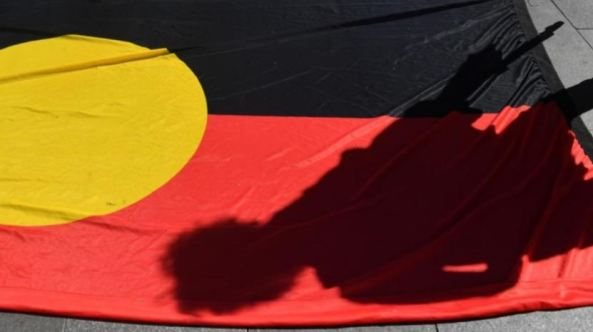 shadow of child cast over Aboriginal flag on the ground