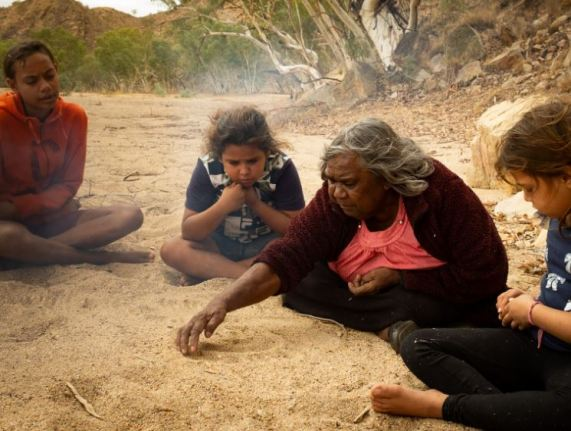 Aboriginal woman cross-legged drawing in riverbed sand for 3 young Aboriginal children