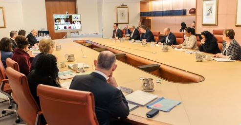 multiple people at large oval desk in Parliament House for second roundtable of senior Ministers & the CoPs