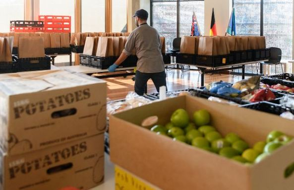 back of worker in hall making up food packages