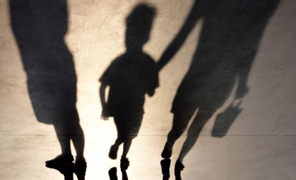 shadow of child holding adult's hand & another adult