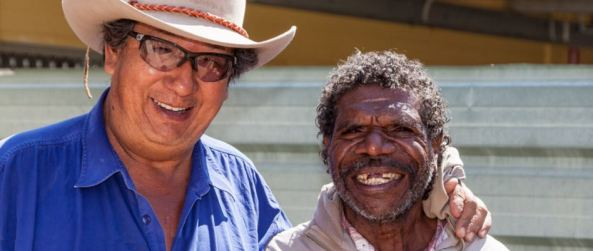 Aboriginal man middle age royal blue collared shirt, sunglasses, akubra with arm around shorter older Aboriginal man in a hoody smiling