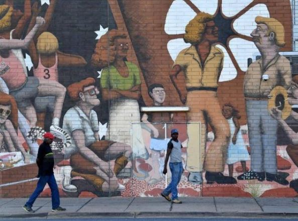 brick wall with mural of Aboriginal people, with 2 Aboriginal men walking past