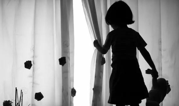black & white image of girl holding teddy in one hand and pulling back a curtain with the other hand