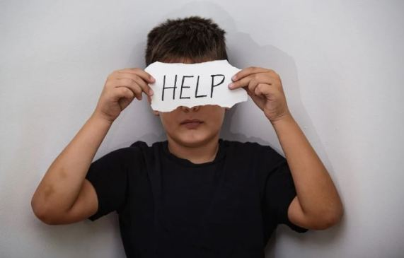 young boy holding ripped piece of paper with the work HELP in front of face