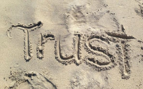 photo of word 'trust' written in the sand