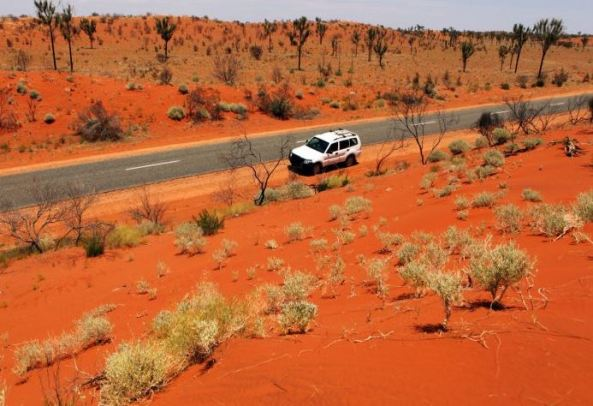 white vehicle on side of bitumen road through red dust landscape