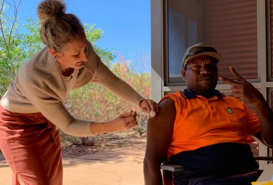 Warmun Community member Luke Banks being vaccinated by Steph Whitwell, Vaccination Nurse from Kununurra COVID-19 Vaccination Clinic