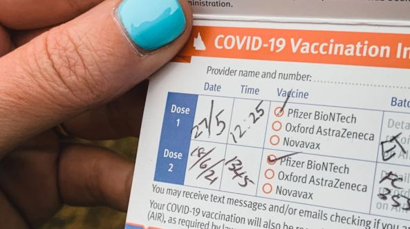 thumb with bright blue nail polish holding COVID-19 vaccination record showing Dose 1 & Dose 2