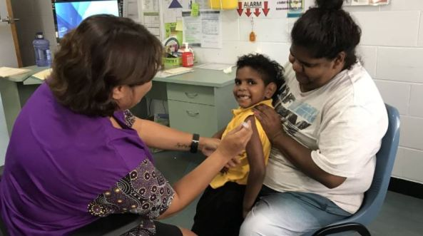 young Aboriginal child on mother's knee getting vaccinated