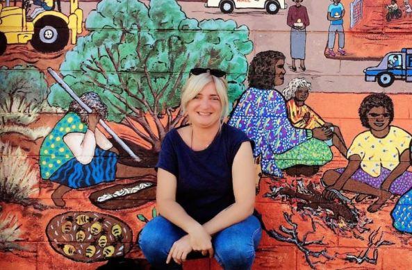 Mena Condo crouching down against Aboriginal art mural