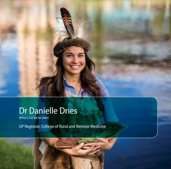 Dr Danielle Dries standing on riverbank with fur headband & feather, stethoscope around neck, holding coolamon with leaves