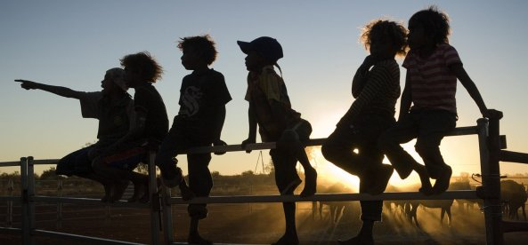Silhouette of Indigenous children sitting on a fence. Image credit: AI / Rusty Stewart