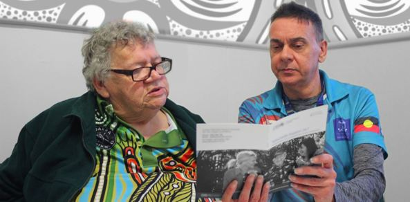 female Elder being shown a booklet by a male health professional