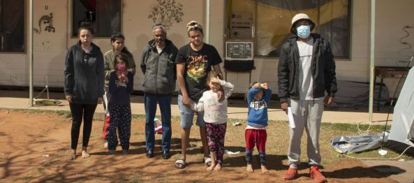 Ronnie Murray & members of his family outside their Wilcannia home & the tent Ron was forced to isolate in