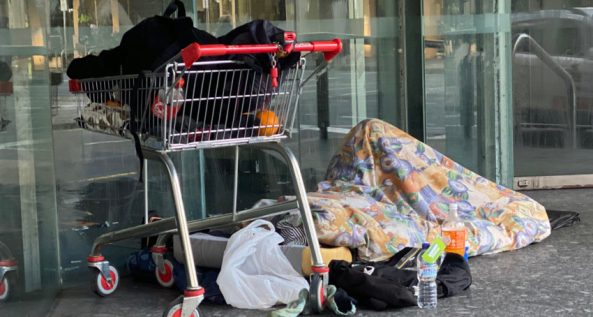 homeless person lying on ground covered entirely with blanket, next to shopping trolley
