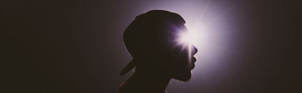 silhouette of Aboriginal man's head with light shining on to eye