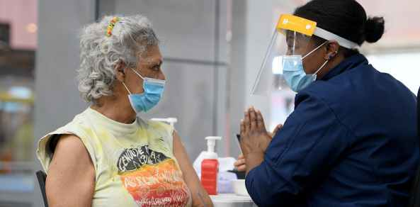 Australian Wiradjuri elder and Indigenous rights activist Aunty Jenny Munro after receiving a covid vaccine. Image source: The Conversation.