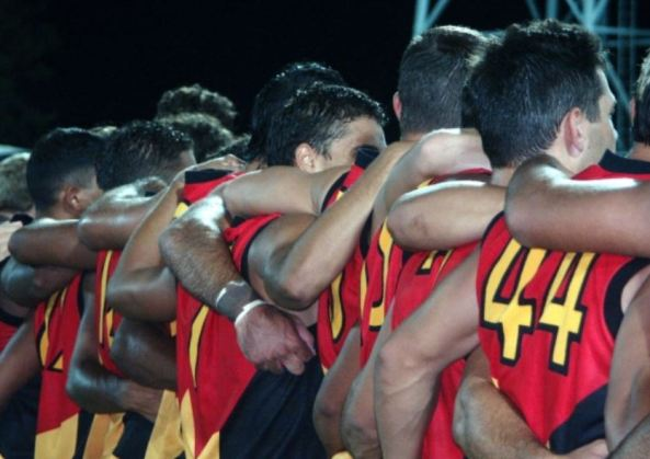 Aboriginal All Stars at Football Park, Darwin - rear view of players with arms around each others waist, neck