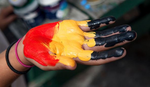 palm of hand painted black yellow red