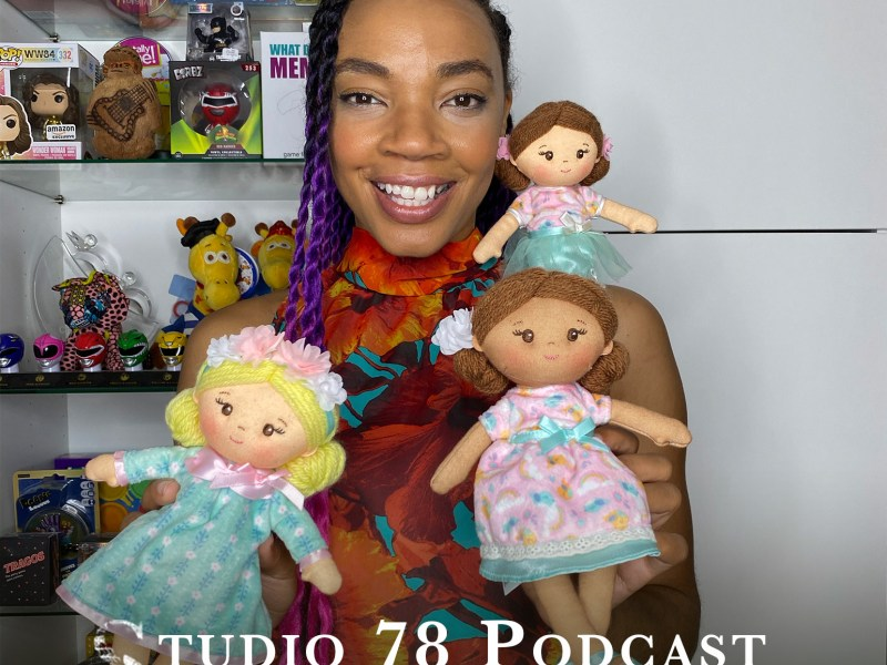 Azhelle Wade, the toy coach, holding up three dolls. She also has multiple shelves of toys behind her.