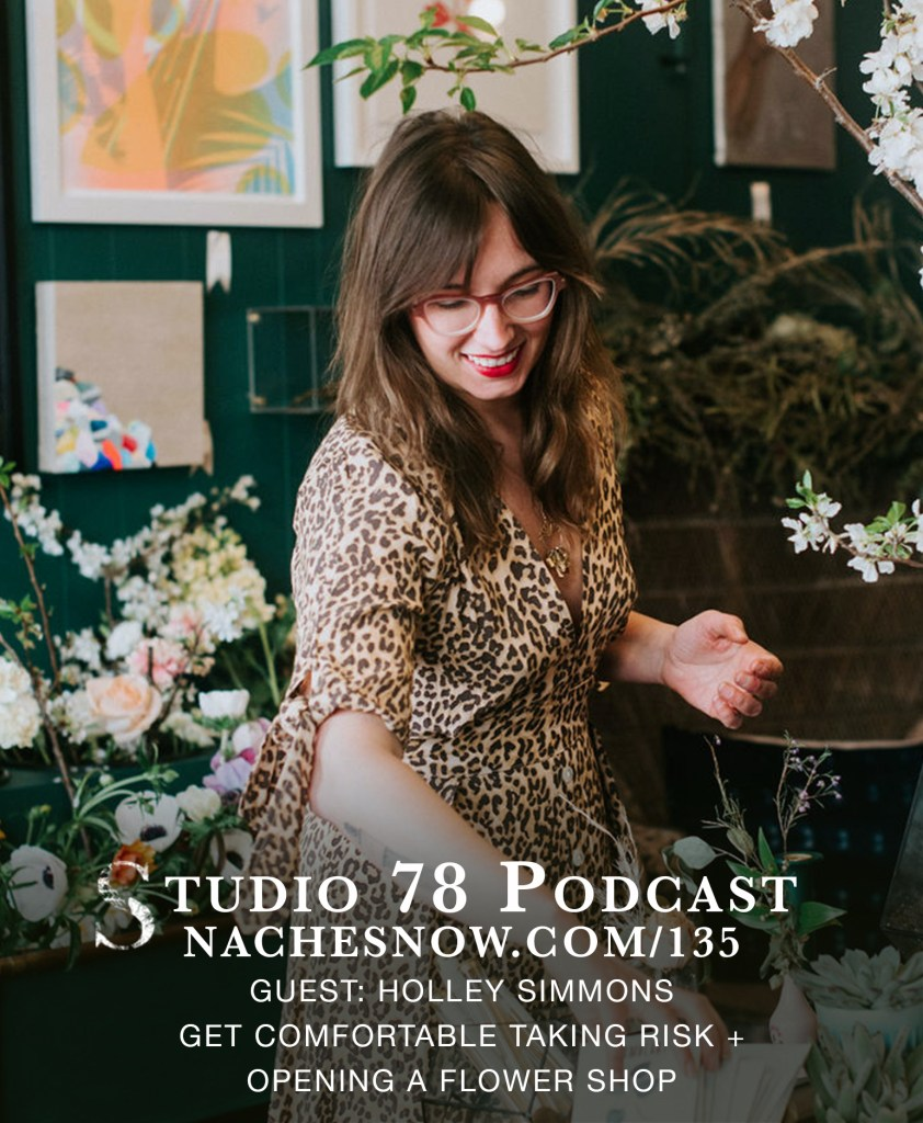Picture of Holley Simmons in a leopard dress watering flowers in her shop. Green wall behind her with multiple frames with artwork.