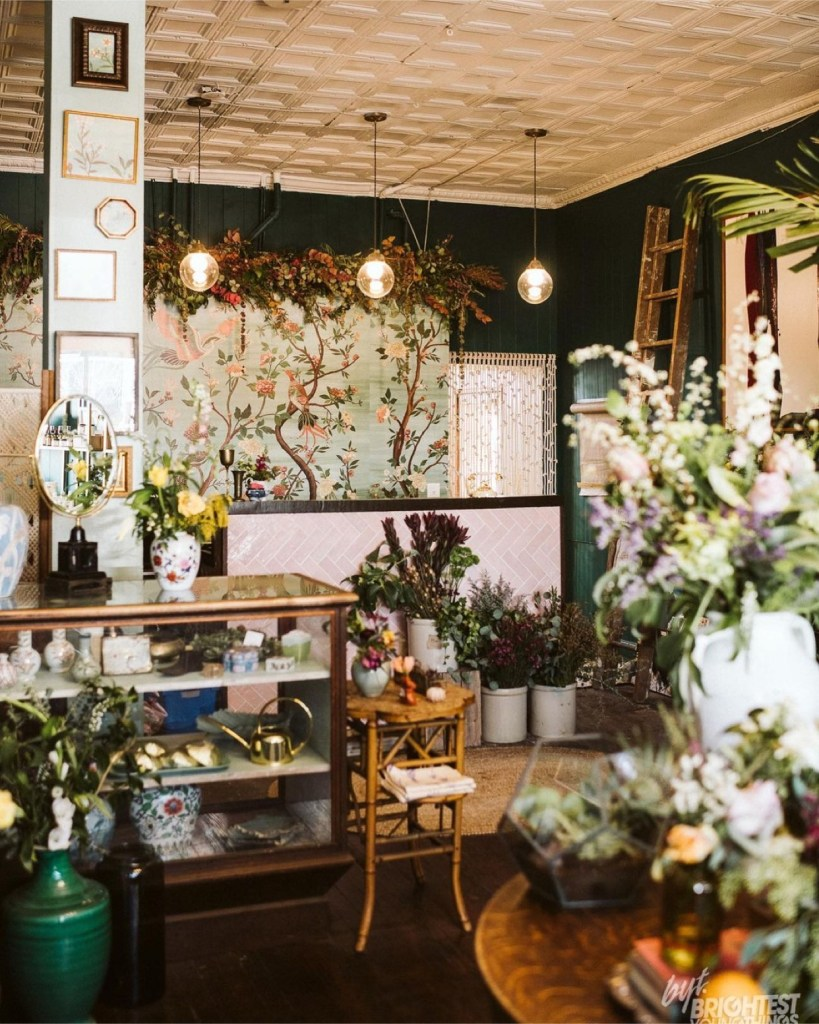 Three globe lights hang in fron of the cashier desk, beautiful mint green wallpaper with trees full of flora garnishes the back wall. You all see a cabinet full of tchotchkes like a gold watering can and boxes.