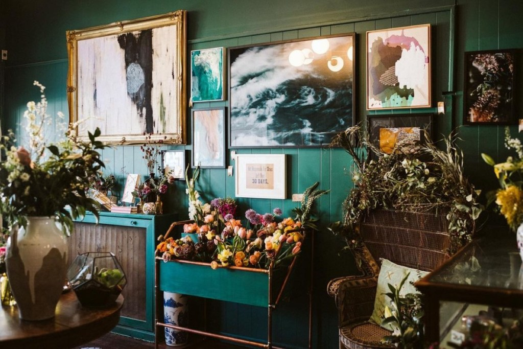 Beautiful greenish blue wall with two large paintings surrounded by four small frames. In front of the wall are lots of colorful flowers and books. You see part of a table that has a vase full of flowers and a terrarium.