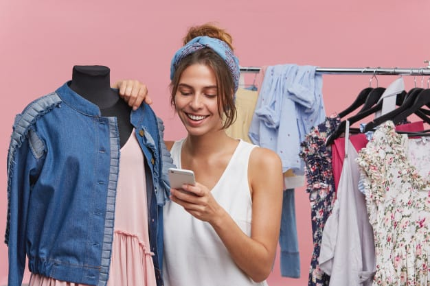 mulher olhando no celular enquando escolhe roupas