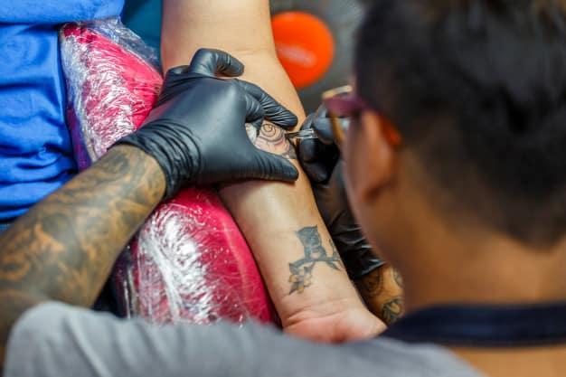 homem fazendo tatuagem