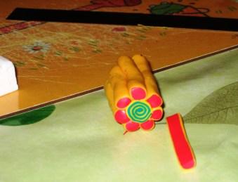 Die rot-gelbe Schlange stückeln, halbieren und als Blütenblätter um die Spirale pappen.