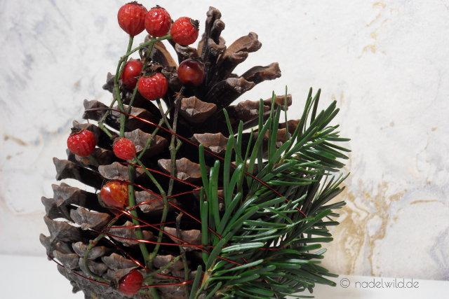Adventsdeko-Kiefernzapfen mit Hagebutte